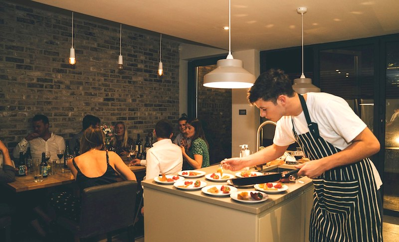 Picture of a dinner party with Jojo from Nomad Cooks as the evening's chef